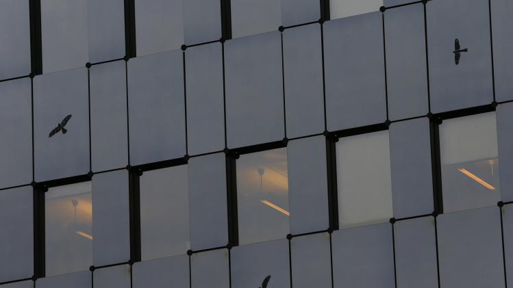 Birds flying past are reflected in a building at the Swiss headquarters of Banque Privee Espirito Santo SA in Pully near Lausanne