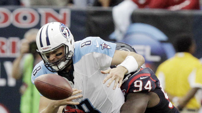 Houston Texans' Antonio Smith (94) knocks the ball loose from Tennessee Titans quarterback Matt Hasselbeck (8) during the fourth quarter of an NFL football game Sunday, Sept. 30, 2012, in Houston. The Texans recovered the ball. (AP Photo/Patric Schneider)