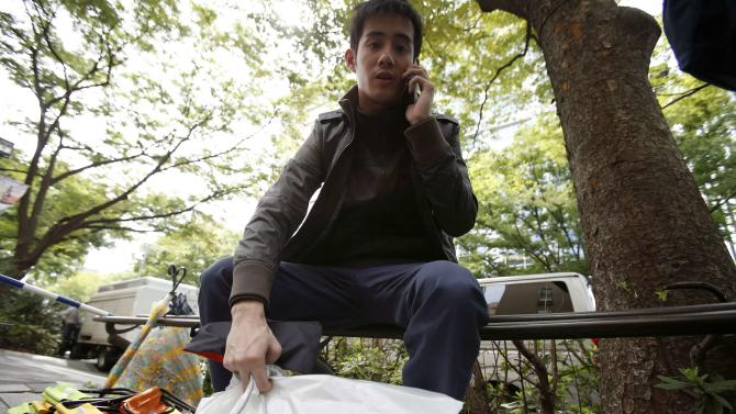 Canadian Jastin Leung uses his mobile phone as he holds plastic bags containing 10 of Apple's new iPhone 6 and 6 plus in front of the Apple Store at Tokyo's Omotesando shopping district