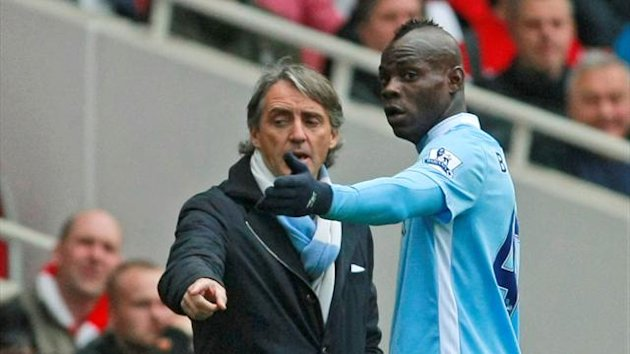 Manchester City's Mario Balotelli, right, speaks to team manager Roberto Mancini during their English Premier League soccer match against Arsenal at the Emirates stadium, London, Saturday, April 8 , 2012.