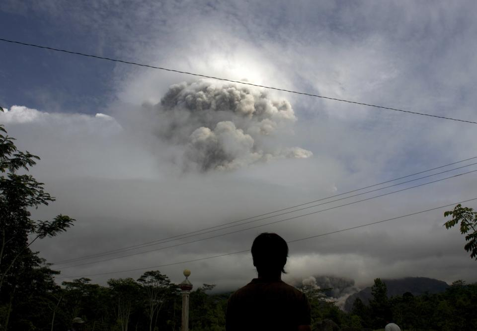 An Indonesian man watches as Mount Merapi erupts in Kepuharjo, Yogyakarta, Indonesia, Wednesday, Nov. 3, 2010. Indonesia's most dangerous volcano is once again sending searing gas clouds and burning rocks down its scorched flanks. (AP Photo/Gembong Nusantara)