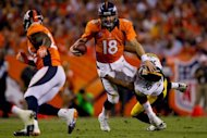 Quarterback Peyton Manning #18 of the Denver Broncos clashes linebacker Larry Foote of the Pittsburgh Steelers during the second quarter on September 9, 2012 in Denver, Colorado. Denver beat the Steelers 31-19