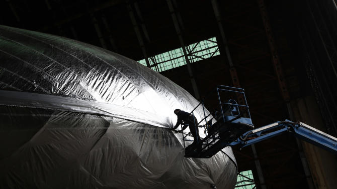 Leonel Cruz pulls down the flab on the Aeroscraft airship, a high-tech prototype airship, in a World War II-era hangar in Tustin, Calif., Thursday, Jan. 24, 2013. Work is almost done on a 230-foot rigid airship inside a blimp hangar at a former military base in Orange Co. The huge cargo-carrying airship is has shiny aluminum skin and a rigid, 230-foot aluminum and carbon fiber skeleton. (AP Photo/Jae C. Hong)