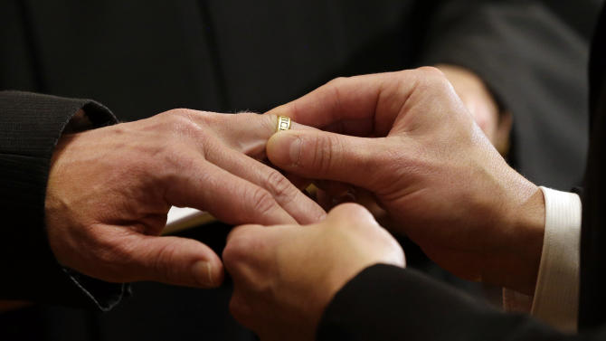 Thomas Rabe, right, places a wedding ring on Robert Coffman's finger during a marriage ceremony at City Hall in Baltimore, Tuesday, Jan. 1, 2013. Same-sex couples in Maryland are now legally permitted to marry under a new law that went into effect after midnight on Tuesday. Maryland is the first state south of the Mason-Dixon Line to approve same-sex marriage. (AP Photo/Patrick Semansky)