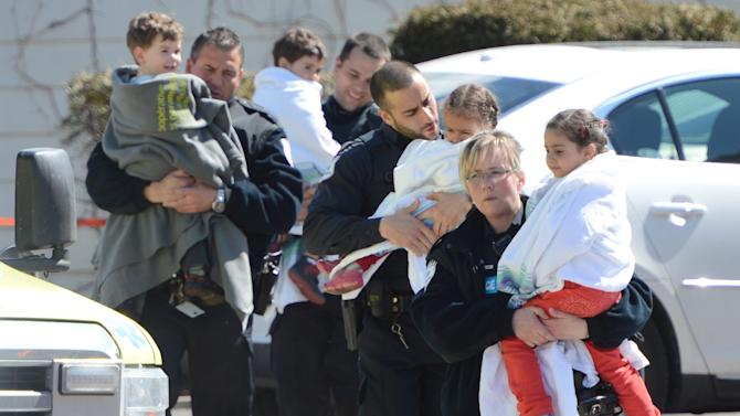 Police carry children from a safehouse to waiting parents and guardians after a shooting at a daycare in Gatineau, Quebec, Canada on Friday April 5, 2013.  Police evacuated children from a daycare center just outside Canada's capital after an adult was killed by gunfire. Gatineau police Lt. Yves Comtois said all 53 children and the teachers were safe and unharmed. The daycare center sits across the street from a hospital in this Quebec city, just across the river from Ottawa. (AP Photo/The Canadian Press, Sean Kilpatrick)