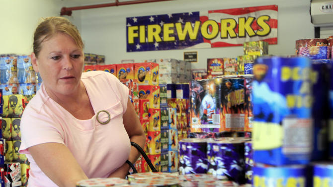 Sheila Grimes of South Berwick, Maine looks through piles of fireworks at Hilltop Fireworks, Tuesday, July 3, 2012 in Somersworth, N.H.   The conventional wisdom is that Maine's new law legalizing consumer fireworks will hurt New Hampshire fireworks stores because Mainers won't have to travel to buy their missiles, Roman candles and exploding aerial displays. But the owners of Hilltop Fireworks in Somersworth, N.H., along the southern Maine border, say they've had more Maine customers in the days leading up to the Fourth of the July than in previous years.(AP Photo/Jim Cole)