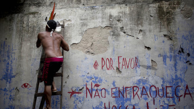 """An Indian man climbs a ladder next to a message that that reads in Portuguese, """"Please, don't weaken our fight,"""" on the site of an old Indian museum, in Rio de Janeiro, Brazil, Saturday, Jan. 12, 2013. Police in riot gear on Saturday surrounded the site, now an indigenous settlement of men and women living in 10 homes, in preparation for their eviction. The settlement is next to the Maracana stadium, pictured in background, which is being refurbished to host the opening and closing ceremonies of the 2016 Olympics and the final match of the 2014 World Cup. The streets around the stadium will also undergo a vast transformation as part of the area's transformation into a shopping and sports entertainment hub. (AP Photo/Felipe Dana)"""