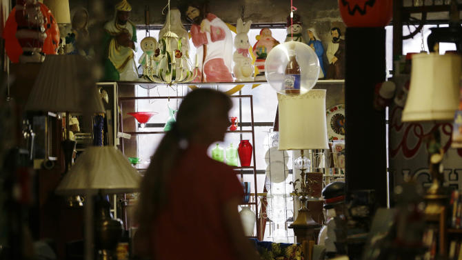 In this April 16, 2015 photo,  Betty Kyzar, of Birmingham, browses through an eclectic collection of 20th century items at What's on 2nd in Birmingham, Ala. The quirky store, a black hole of kitsch, has become a favorite of residents and visitors alike since it opened eight years ago. The store is a great, time-sucking stop for business travelers with a couple of hours or an entire day to kill. (AP Photo/Brynn Anderson)