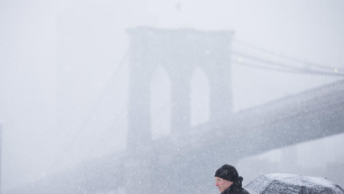 People wait on a ferry boat in view of the Brooklyn Bridge, during a winter snowstorm Monday, Feb. 3, 2014, in the Brooklyn borough of New York. After several days of milder weather, snow has returned to the Northeast. (AP Photo/Matt Rourke)