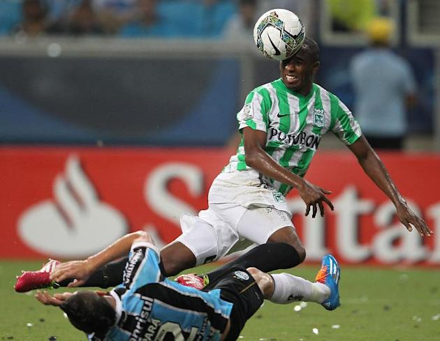 Juan Valencia of Colombia's Atletico Nacional, top, heads the ball past Para of Brazil's Gremio during a Copa Libertadores soccer game in Porto Alegre, Brazil, Tuesday, Feb.25, 2014