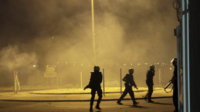 """Riot police fire tear gas and stun grenades to disperse villagers gathering near the site in Sadad, Bahrain, early Saturday, Sept. 29, 2012, where a youth was killed during an anti-government protest, allegedly by police shotgun fire. An Interior Ministry statement said a police patrol was attacked with petrol bombs and iron rods late Friday, and one person died when """"policemen defended themselves."""" A witness among protesters said demonstrators were marching against the government when a policeman suddenly stepped out near the youth and shot him at close range. (AP Photo/Hasan Jamali)"""