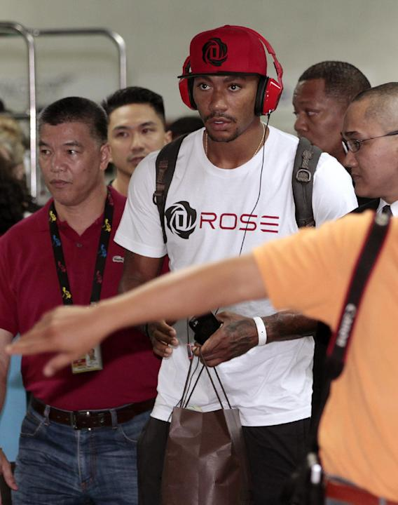 NBA star Derrick Rose of Chicago Bulls, center, walks at the arrival area of Manila's International Airport, Philippines on Saturday, Sept. 14, 2013. Rose is in the country as part of the Asia leg of