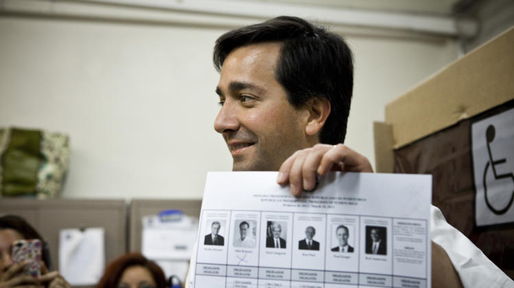 "Puerto Rico's Governor Luis Fortuno shows his ballot to the press after marking it with an ""x"" under the photo of candidate Mitt Romney during the Republican presidential primary election at San Jose Academy in Guaynabo, Puerto Rico, Sunday March 18, 2012. Puerto Rico's residents cannot vote in general elections, but are set to award 20 delegates in their Sunday Republican primary.  (AP Photo/Christopher Gregory)"