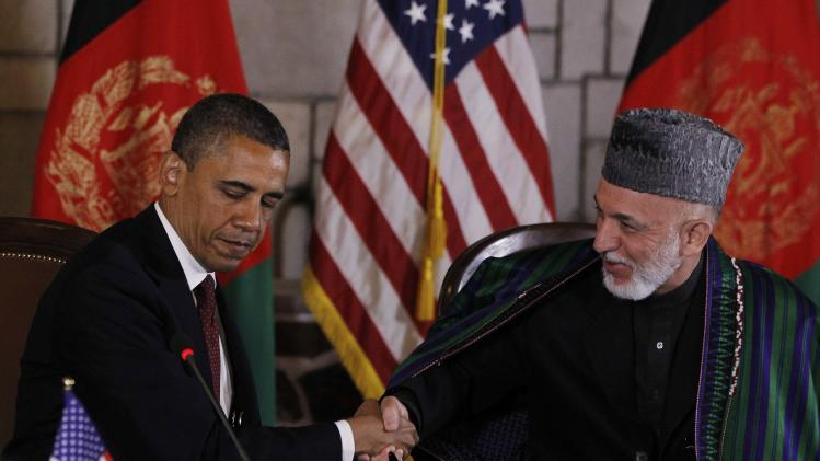 President Barack Obama and Afghan President Hamid Karzai shake hands after making statements before signing a strategic partnership agreement at the presidential palace in Kabul, Afghanistan, Wednesday, May 2, 2012. (AP Photo/Charles Dharapak)