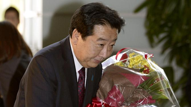 Japan's Prime Minister Yoshihiko Noda, holding flowers, bows as he leaves the prime minister's office in Tokyo, Wednesday, Dec. 26, 2012.  Prime Minister Noda's Cabinet resigned Wednesday to clear the way for a vote in parliament to formally install the nation's new leader, Shinzo Abe, a conservative whose nationalist positions have in the past angered Japan's neighbors. (AP Photo/Kyodo News) JAPAN OUT, MANDATORY CREDIT, NO LICENSING IN CHINA, HONG KONG, JAPAN, SOUTH KOREA AND FRANCE
