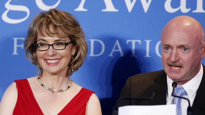 Capt. Mark Kelly speaks next to his wife, former Arizona congresswoman Gabrielle Giffords after Giffords received the John F. Kennedy Profile in Courage Award at the JFK Library in Boston, Sunday, May 5, 2013. (AP Photo/Michael Dwyer)