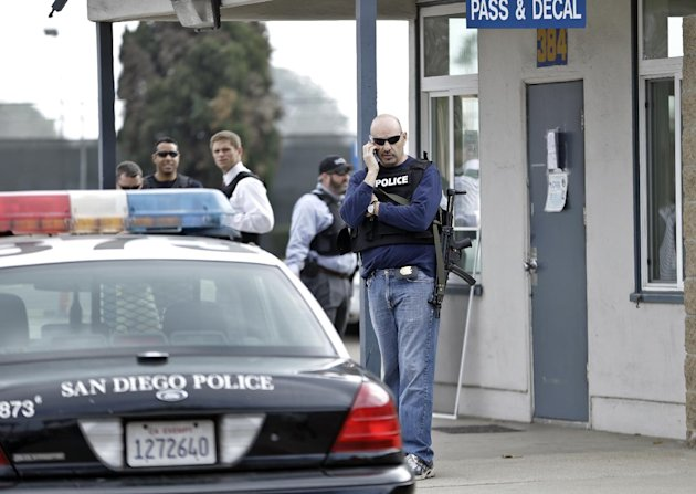 San Diego police officers and federal agents occupy the gate to the Point Loma Naval facility in San Diego Thursday Feb. 7, 2013 during a manhunt for former Los Angeles officer Christopher Dorner in S