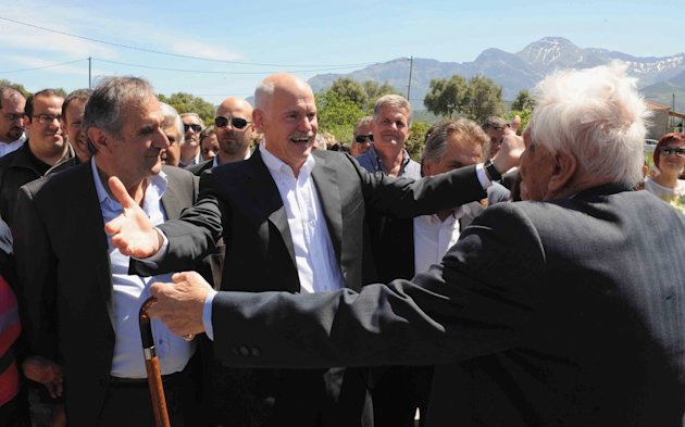 Former Socialist Prime Minister George Papandreou, 2nd left, is welcomed by supporters prior to casting his ballot in Kalentzi, western Greece Sunday May 6, 2012. Greeks head to the polls Sunday in th