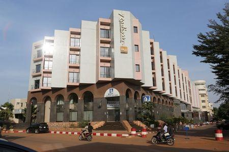 People drive motorcycles past the Radisson Blu hotel in Bamako
