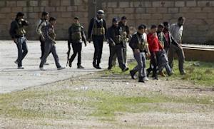 Members of Free Syrian Army walk with new youth recruits in northern Syrian town of Ras al-Ain, as seen from Turkish border town of Ceylanpinar,