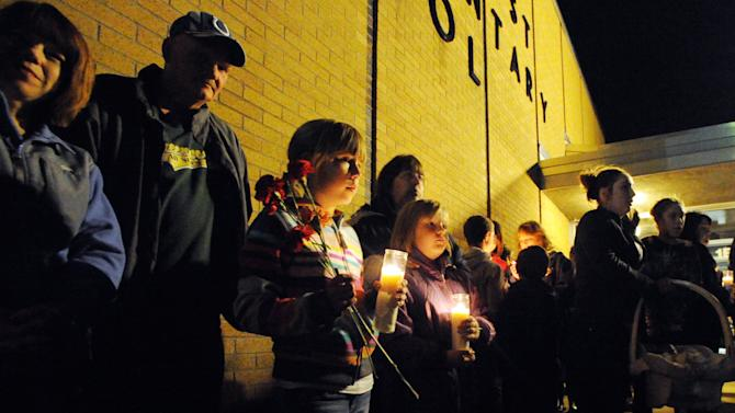A crowd gathers during a candlelight vigil, Sunday, Nov. 11, 2012, at Southwest Elementary School in Greenwood, Ind., for teacher Jennifer Longworth. Officials did not identify the two people who were killed in a blast on Saturday. However, a candlelight vigil was held for second-grade teacher Jennifer Longworth. She and her husband, John Dion Longworth, lived at a home destroyed in the blast. (AP Photo/The Indianapolis Star, Rob Goebel)