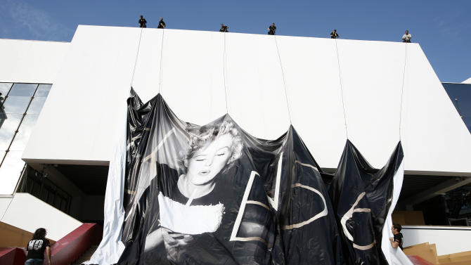 Workers set up a giant 65th Cannes Film Festival official poster showing Marilyn Monroe on the Cannes Festival Palace, Monday, May 14, 2012. The Cannes Film Festival will start on Wednesday, May 16.(AP Photo/Lionel Cironneau)