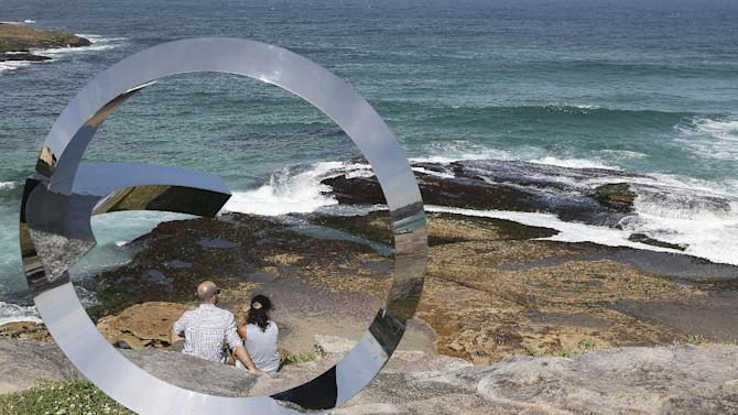 "A couple sit on rocks near a sculpture titled ""Wind Stone - The Threshold of Consciousness"" created by artist Koichi Ishino at Sculpture By The Sea in Sydney, Australia, Friday, Oct. 24, 2014. Sculptures and other art forms created by 109 artists from 16 countries, are displayed across the costal area of Sydney. (AP Photo/Rob Griffith)"