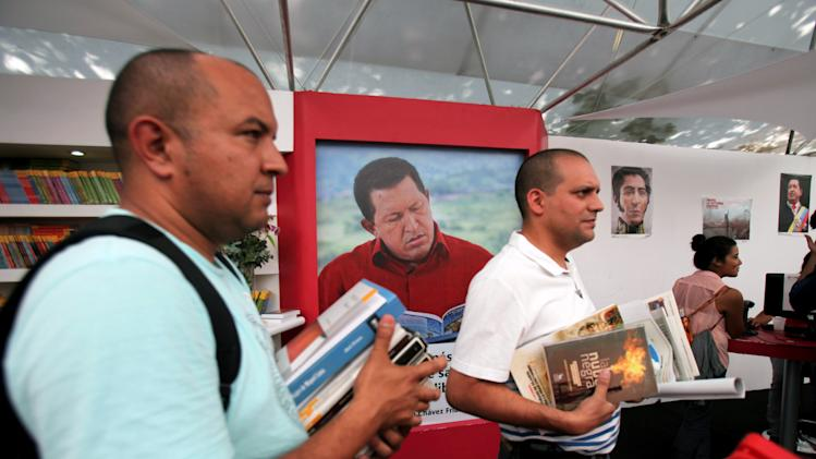 Customers line up with books at the annual book fair where a photo of Venezuela's former President Hugo Chavez hangs inside a book store in Caracas, Venezuela, Tuesday, March 19, 2013. (AP Photo/Fernando Llano)