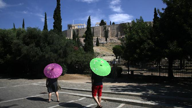 Tourists hold umbrellas to protect from the sun as they enjoy a walk under the ancient Acropolis hill in Athens, Tuesday, June 30, 2015. On the streets of the Greek capital, resplendent in the early days of summer, there's still a veneer of normalcy - at least for foreigners. But for locals, the miserly 60 euros ($67) per day cash limit at ATMs makes it difficult to run a small business or keep a family going. (AP Photo/Spyros Tsakiris)