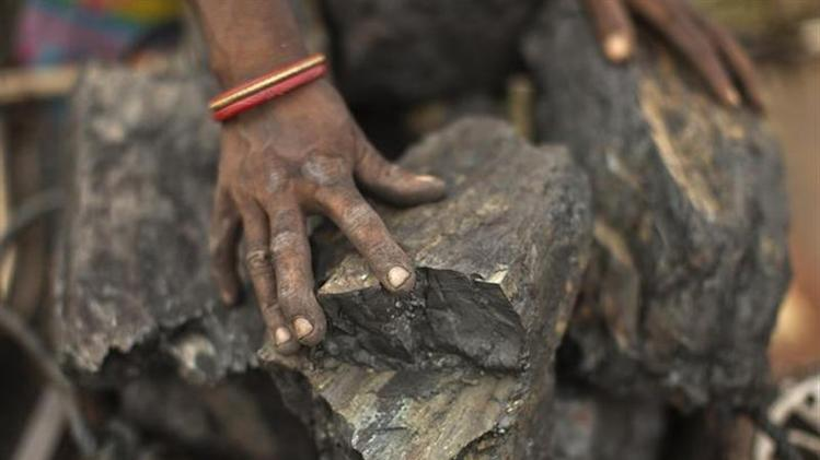 A local woman prepares to carry coal at an open coal field at Dhanbad district in the eastern Indian state of Jharkhand September 19, 2012. REUTERS/Ahmad Masood/Files