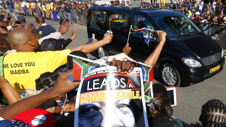 People react as the hearse carrying the coffin of former South African President Nelson Mandela travels through a street in Pretoria