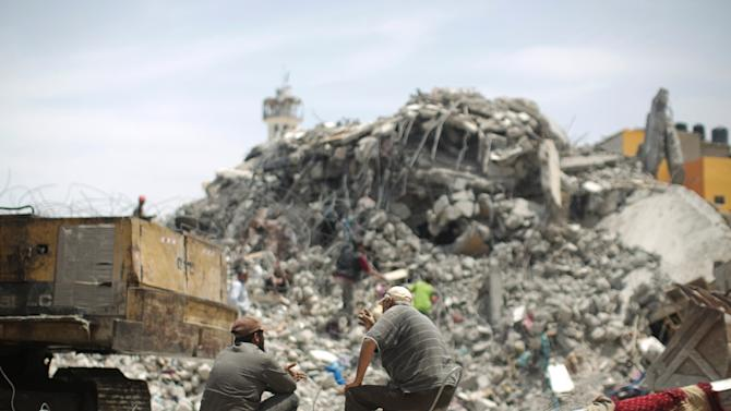 Palestinian men sit amid the rubble of houses which were destroyed during the 50-day war between Israel and Hamas militants in the summer of 2014, in the Eastern Gaza City Shujaiya neighbourhood, on May 23, 2015