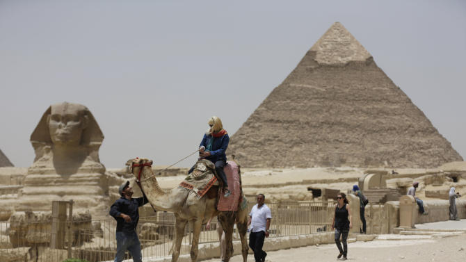"""In this photo taken Friday, May 31, 2013, a tourist takes a camel ride at the Giza Pyramids in Giza, Egypt. A statement by Egypt's Antiquities' Ministry Saturday, June 1, 2013 says a U.S. Embassy security warning sent to citizens to be extra cautious for their safety in the area of the Pyramids is baseless. Earlier in the week, the U.S. Embassy in Cairo sent a message to its citizens warning them to """"elevate their situational awareness when traveling to the Pyramids"""" due to a """"lack of visible security or police"""" in the area. (AP Photo/Hiro Komae)"""