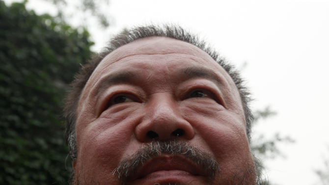 Dissident artist Ai Weiwei speaks to journalists after a verdict was announced in his lawsuit against the Beijing tax authorities in Beijing, China, Friday, July 20, 2012. A Beijing court on Friday rejected an appeal by artist and government critic Ai against a more than $2 million fine for tax evasion, which he says is part of an intimidation campaign to stop him from criticizing the government. (AP Photo/Ng Han Guan)