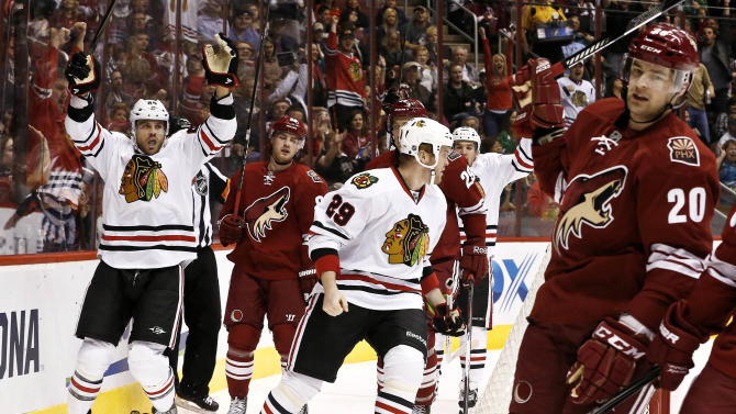 Chicago Blackhawks' Viktor Stalberg (25), of Sweden, celebrates his goal with teammate Bryan Bickell (29) as Phoenix Coyotes' Chris Summers (20) and Mikkel Boedker, second from left, of Denmark, show their frustration during the first period in an NHL hockey game Thursday, Feb. 7, 2013, in Glendale, Ariz.(AP Photo/Ross D. Franklin)