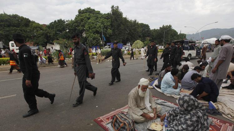 Policemen walk past supporters of Tahir ul-Qadri, Sufi cleric and leader of political party Pakistan Awami Tehreek (PAT), having their breakfast in front of the Parliament house building during the Revolution March in Islamabad