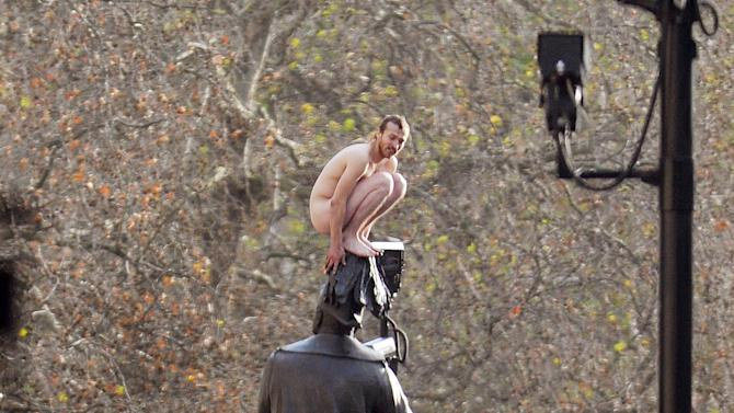 """A naked man sits on top of a statue of George, Duke of Cambridge in Whitehall, London, Friday Nov. 23, 2012.  Police and eyewitnesses say a naked man has climbed atop an equestrian statue in the heart of Whitehall, London's government district. A Scotland Yard spokesman said that the man, believed to be in his 30s or 40s, has been sitting atop the statue for the better part of two hours. He said Friday: """"We're still talking to him. We're still trying to get him down without causing any injury to him."""" (AP Photo/ John Stillwell/PA) UNITED KINGDOM OUT"""