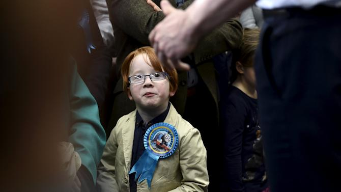 A boy looks up as Britain's Prime Minister Cameron addresses party activists at a campaign rally in Carlisle in northern England