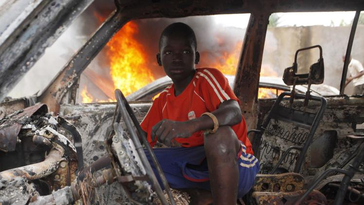 A Christian youth squats inside a burnt out car in Bangui