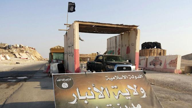 """In this Tuesday, July 22, 2014 photo, a sign is posted at a checkpoint belonging to the Islamic State group, captured from the Iraqi Army, at the main entrance of Rawah, 175 miles (281 kilometers) northwest of Baghdad, Iraq. Arabic reads,""""Islamic State, the Emirate of Anbar, City of Rawah."""" It has been nearly six weeks since a Sunni militant blitz led by the Islamic State extremist group seized large swaths of northern and western Iraq. (AP Photo) (AP Photo)"""