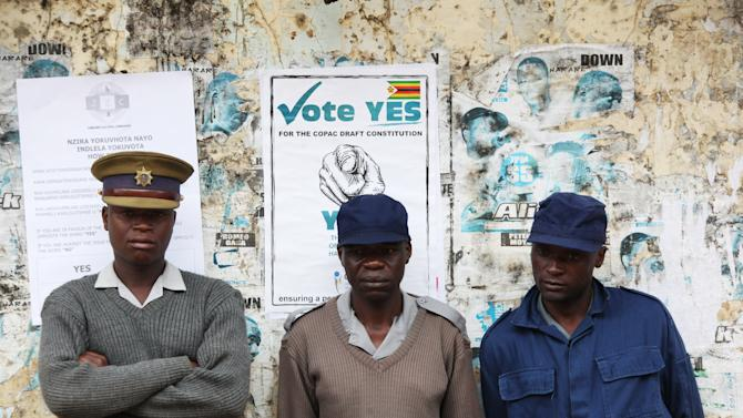 Police officers stand at a Polling station during a referendum in Harare, Zimbabwe, Saturday, March, 16, 2013. The referendum this weekend mirrors the hopes and fears of four previous elections which were marred by violence and vote-rigging since Tsvangirai, a former labor leader, founded his Movement for Democratic Change party, the first real challenge to Mugabe, in 1999. (AP Photo/Tsvangirayi Mukwazhi)