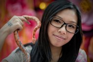 A woman displays her pet, a corn snake, during an event promoting responsible breeding and pet ownership, in Kong Kong, on January 10, 2013. As Hong Kong prepares to usher in the Year of the Snake, an increasing number of the reptiles are slithering their way into local households, with sales of the uncuddly pet rocketing