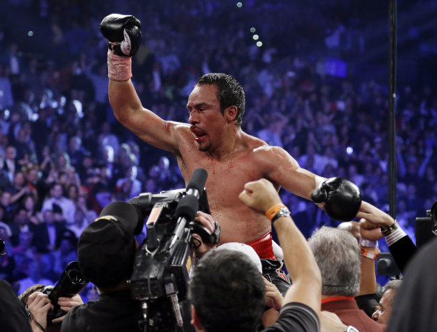 Juan Manuel Marquez, from Mexico, celebrates his sixth round knockout victory over Manny Pacquiao, from the Philippines, in their WBO world welterweight  fight Saturday, Dec. 8, 2012, in Las Vegas.  (
