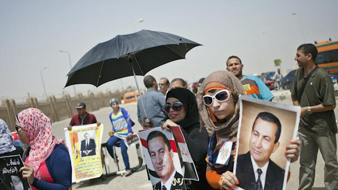 Supporters holding pictures of Egypt's ousted President Hosni Mubarak rally outside a courtroom in Cairo, Saturday, June 8, 2013. (AP Photo/Khalil Hamra)