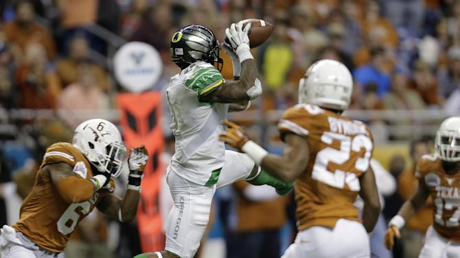 Oregon's Josh Huff, center, pulls in a pass as Texas' Quandre Diggs (6) defends during the second half of the Valero Alamo Bowl NCAA college football game, Monday, Dec. 30, 2013, in San Antonio. Oregon won 30-7. (AP Photo/Eric Gay)