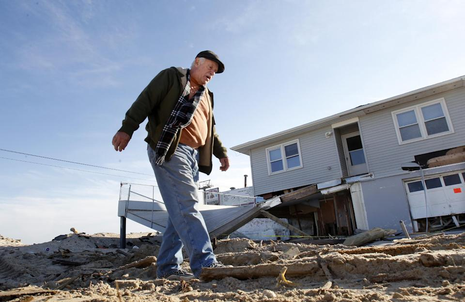 Henny Mauro walks in Seaside Heights, N.J., Thursday, Jan. 3, 2013,  past a beach-side home that was destroyed by Superstorm Sandy.  Under intense pressure from angry Republicans, House Speaker John Boehner has agreed to a vote this week on aid for Superstorm Sandy recovery.  (AP Photo/Mel Evans)