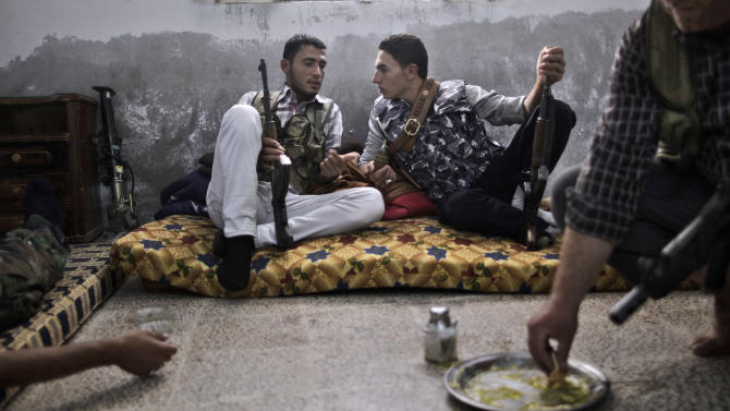 Syrian rebel fighters eat and chat as they wait for transportation to go and fight government forces in Aleppo, at their headquarters in Suran, on the outskirts of Aleppo, Syria, Monday, Sept. 10, 2012. (AP Photo/Muhammed Muheisen)