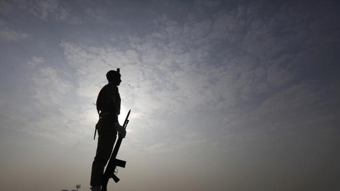 A cadet from Pakistan Military Academy is silhouetted against the sun while stands guard during a ceremony to mark 138th birth anniversary of Mohammad Ali Jinnah at his mausoleum in Karachi