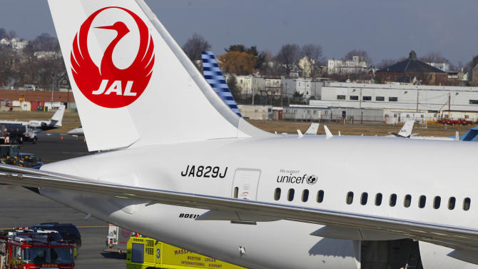 A Japan Airlines Boeing 787 Dreamliner jet aircraft is surrounded by emergency vehicles while parked at a terminal E gate at Logan International Airport in Boston as a fire chief looks into the cargo hold Monday, Jan. 7, 2013. A small electrical fire filled the cabin of the JAL aircraft with smoke Monday morning about 15 minutes after it landed in Boston. (AP Photo/Stephan Savoia)
