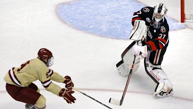 Northeastern goalie Chris Rawlings, right, clears the puck as he is pressured by Boston College forward Brendan Silk during the first period of the championship game at the Beanpot college hockey tournament in Boston, Monday, Feb. 11, 2013. (AP Photo/Charles Krupa)